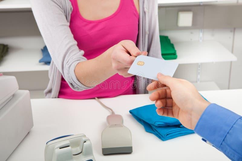 Kunde, der Kreditkarte zu einem Kassierer überreicht lizenzfreie stockfotos