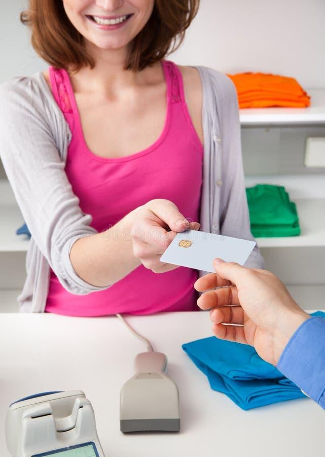 Kunde, der Kreditkarte zu einem Kassierer überreicht stockfotos