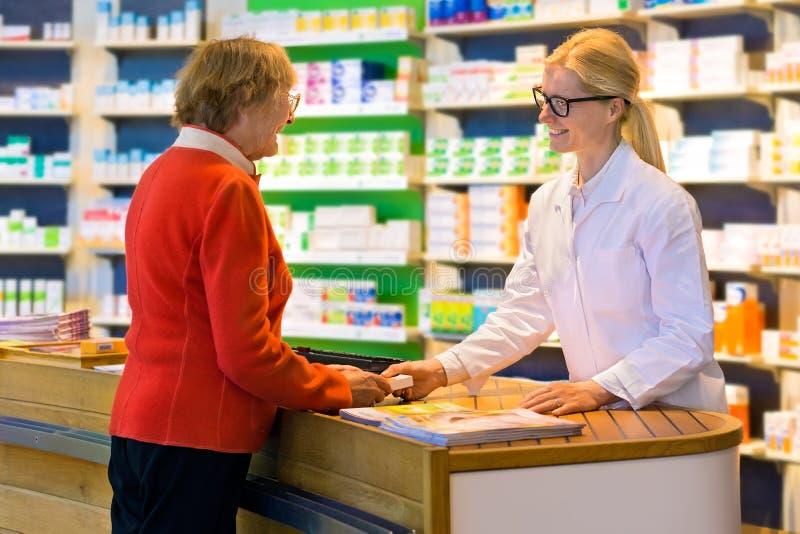 Kunde, der Medikation vom Apotheker bekommt lizenzfreie stockfotografie