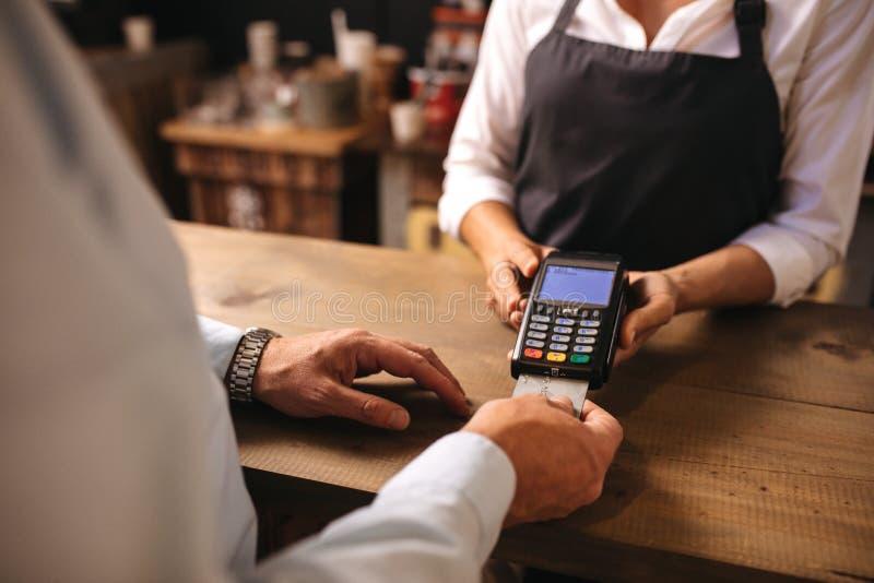 Kunde, der mit Kreditkarte Zahlung des Kaffees am Café tut stockbild
