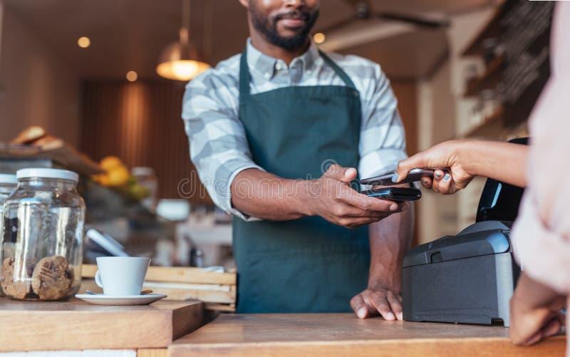 Kunde, der nfc Technologie einsetzt, um für ihren Cafékauf zu zahlen stockbild