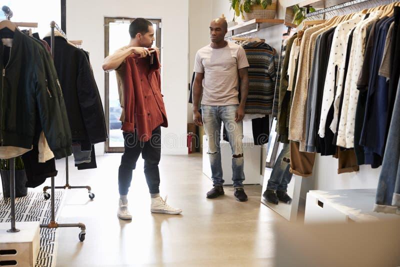 Kunde halten Kleidung in einem Shop, während Assistent an schaut stockbild