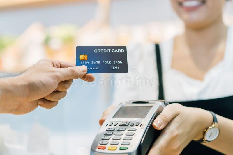 Kunde im Café zahlt dem Verkäufer über die Kreditkarte lizenzfreie stockbilder