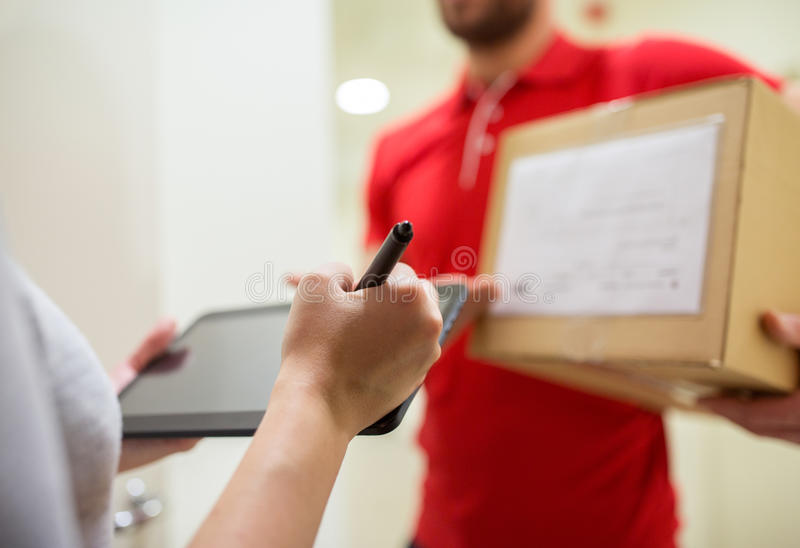 Kunde mit Tabletten-PC unterzeichnend für Paket stockbilder