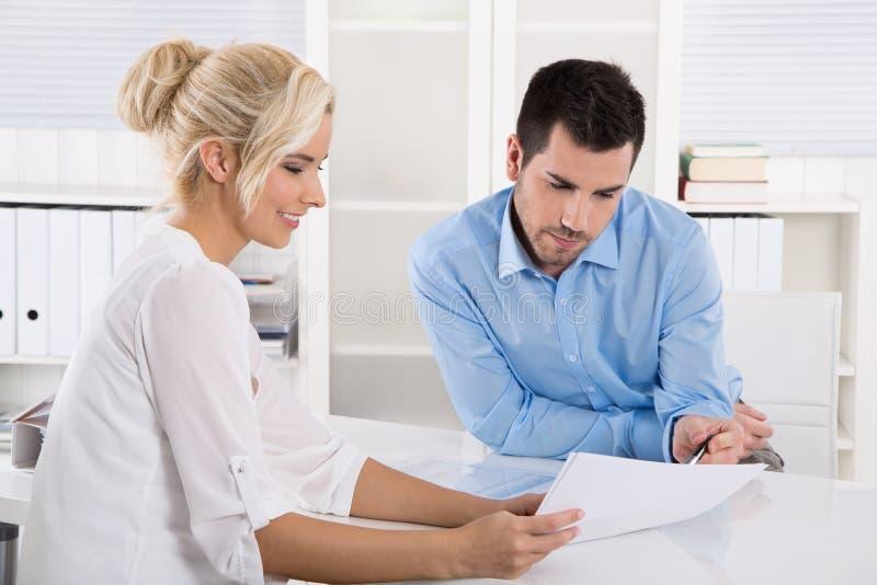 Kunde und Kunde, die am Schreibtisch oder an Geschäftsleuten sprechen a sitzt lizenzfreies stockbild
