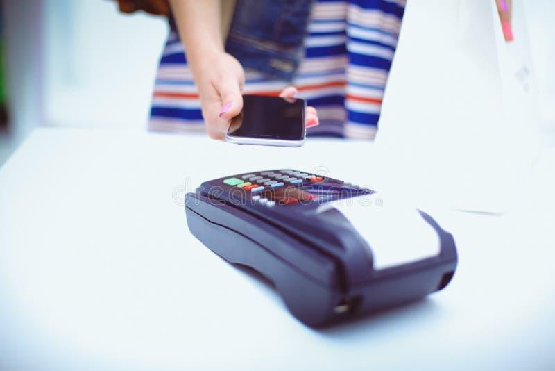 Kunden betalar med smartphonen shoppar in genom att använda NFC-teknologi Nfc teknologi Kunden betalar fotografering för bildbyråer