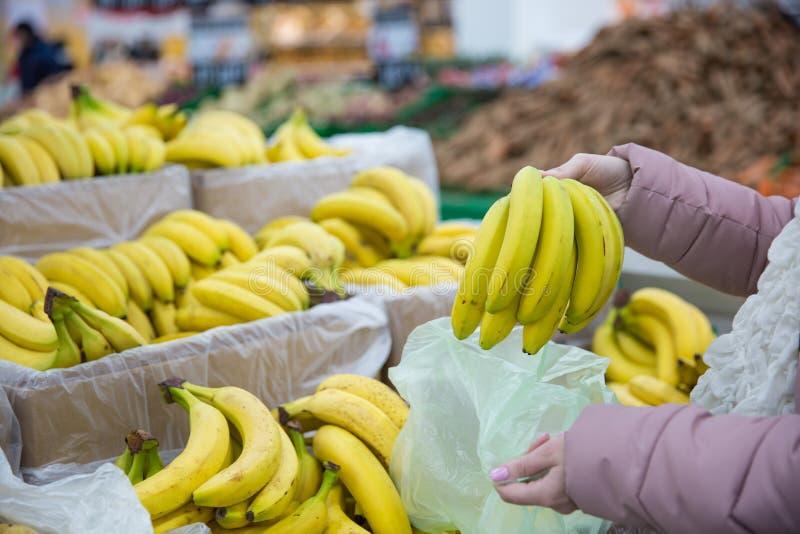 Kunden beundrar mogna bananer av bananer arkivbild