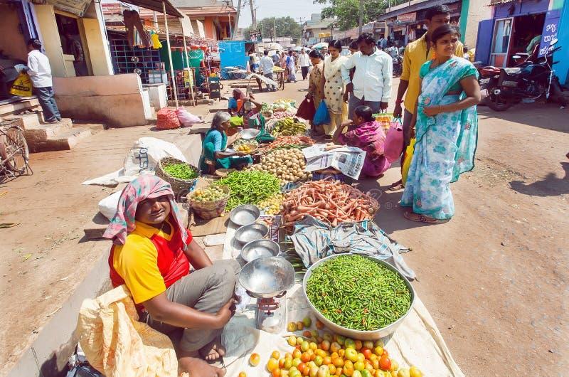 Kunden in den Trachtenkleidern frische grüne Erbsen, Kartoffeln, Karotten kaufend am Markt der indischen Straße stockbild