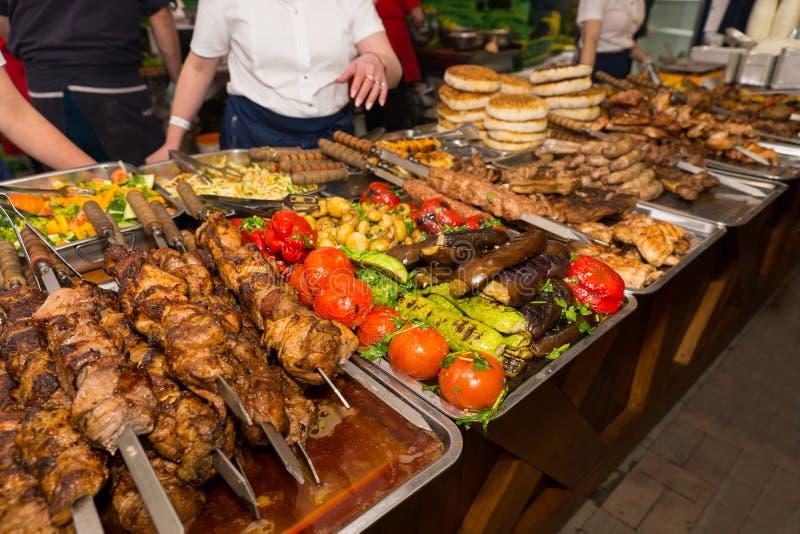 Kunden, die Fleisch und Gemüse vom Buffet wählen stockfotografie