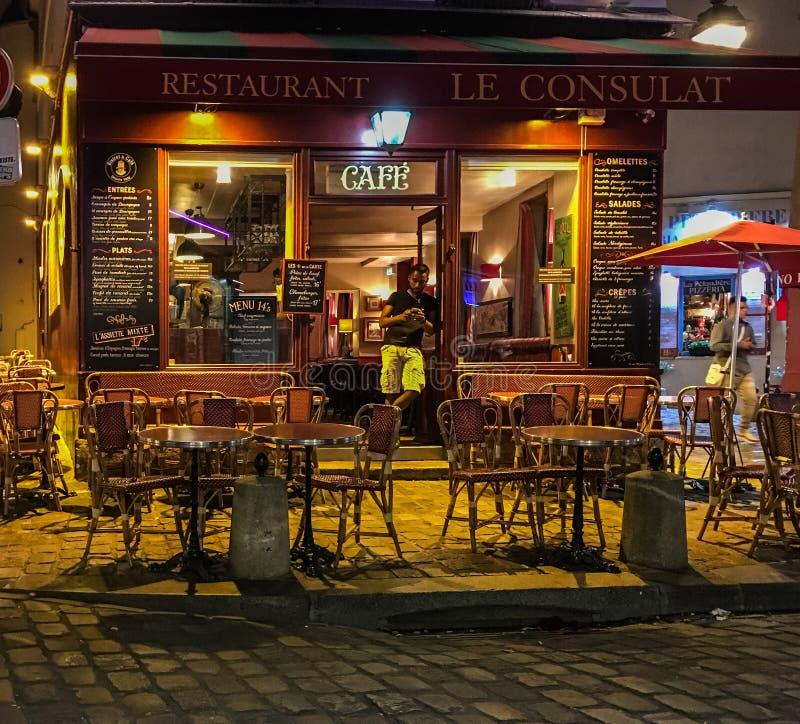 Kunden lutar i dörröppning av den Le Consulat restaurangen i Paris royaltyfria bilder