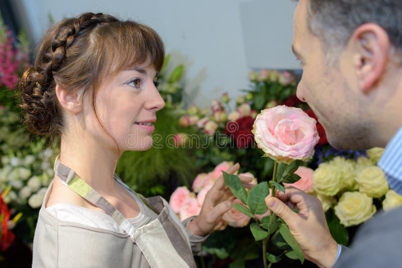 Kunden med att lukta för blomsterhandlare steg arkivfoto