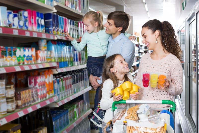 Kunden mit den Kindern, die süße Milchprodukte in Hyper vorwählen lizenzfreies stockbild