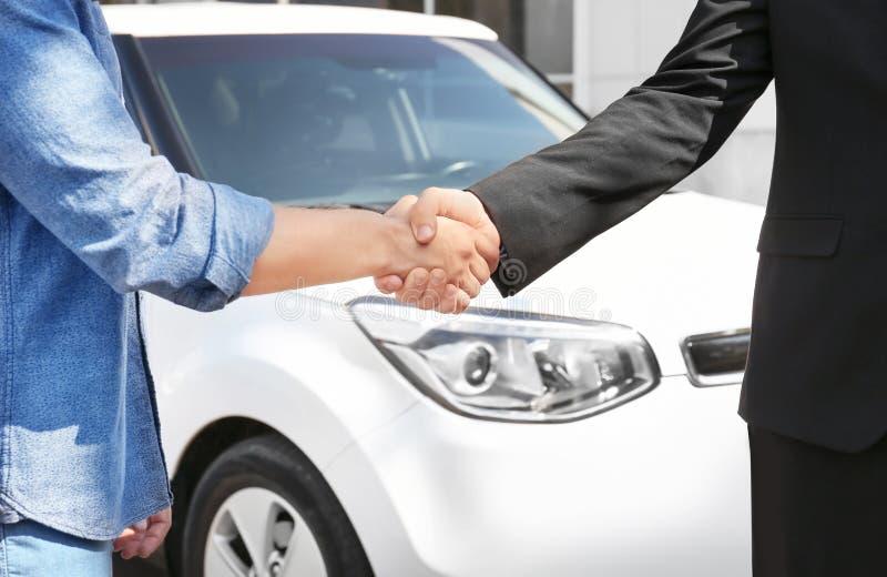 Kunden och representanten som skakar händer, near den nya bilen arkivbilder