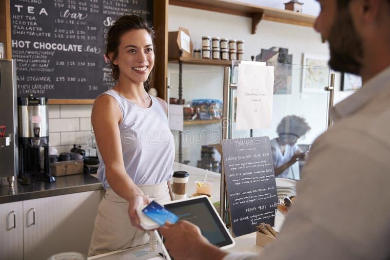 Kunden på coffee shop betalar le servitrins med kortet arkivfoto