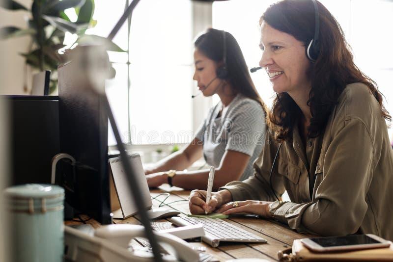 Kundendienstarbeitskräfte, die vor dem Computerarbeiten sitzen stockfotos