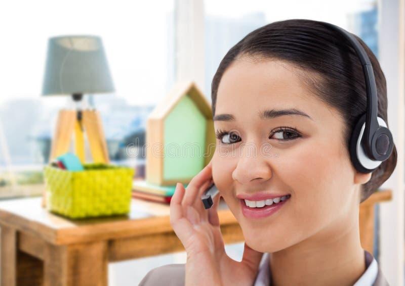 Kundendienstfrau mit Kopfhörer im hellen Büro lizenzfreies stockbild
