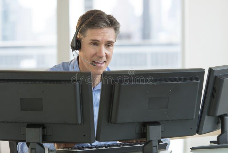 Kundendienstmitarbeiter Using Multiple Screens stockbild