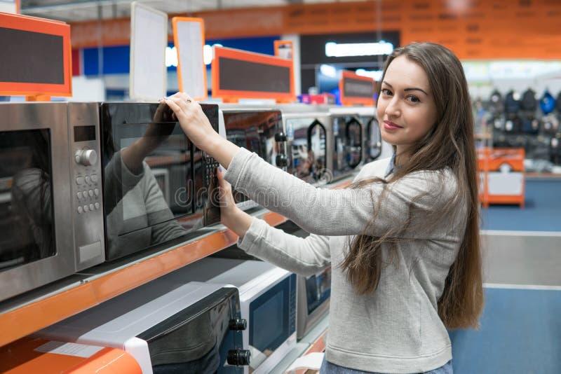 Kundenmädchen wählt einen Mikrowellenherd in einem Haushaltsgerätspeicher stockbild