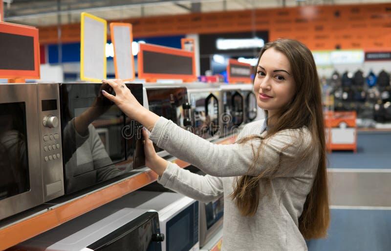 Kundenmädchen wählt einen Mikrowellenherd in einem Haushaltsgerätspeicher stockfoto