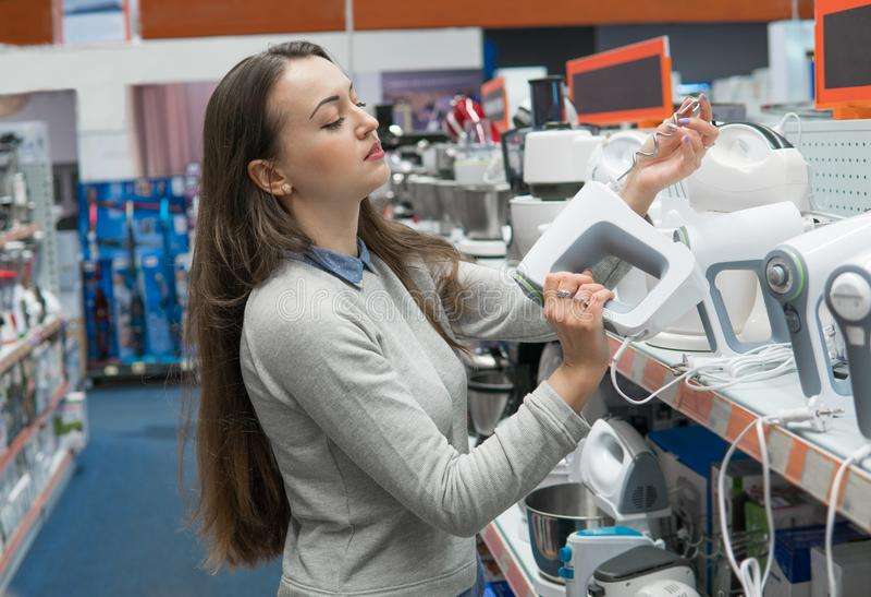 Kundenmädchen wählt einen Mischer oder eine Mischmaschine in einem Haushaltsgerätspeicher stockfotografie