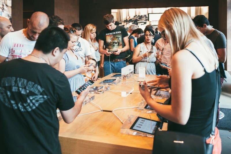 Kunder inom Apple Store som beundrar latesiPhonen arkivfoton