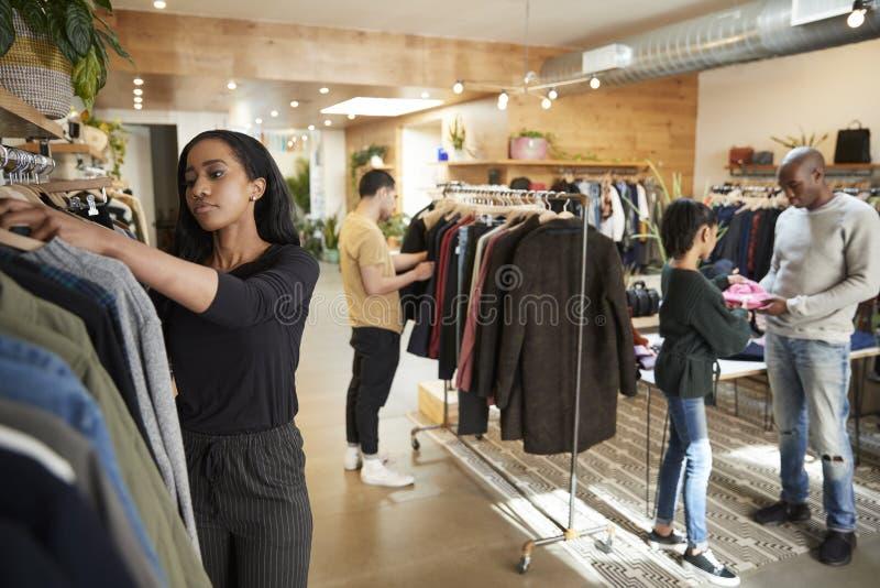 Kunder och personalen i upptagen kläder shoppar royaltyfri bild