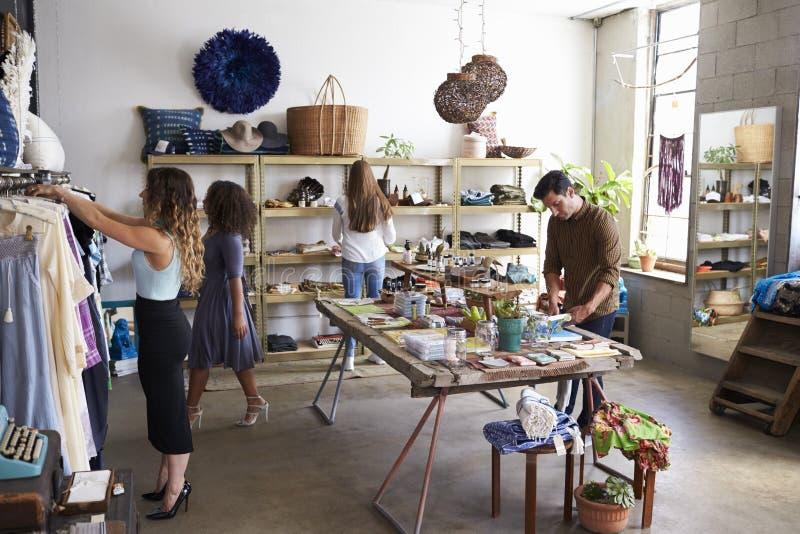 Kunder och personalen i upptagen kläder shoppar royaltyfri fotografi