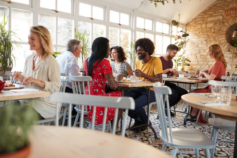 Kunder som äter på en upptagen restaurang i dagtiden royaltyfri fotografi