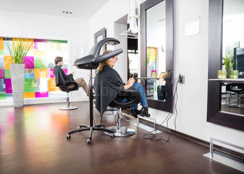 Kunder som genomgår hårbehandling i mottagningsrum fotografering för bildbyråer