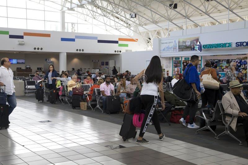 Kunder väntar på flyg på den Luis Munoz Marin San Juan flygplatsen i Puerto Rico royaltyfri bild