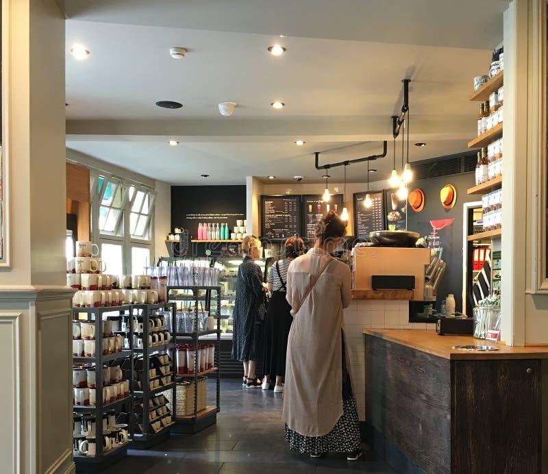 Kunder väntar på service i ett Starbucks lager på Montmartre i Paris arkivfoton
