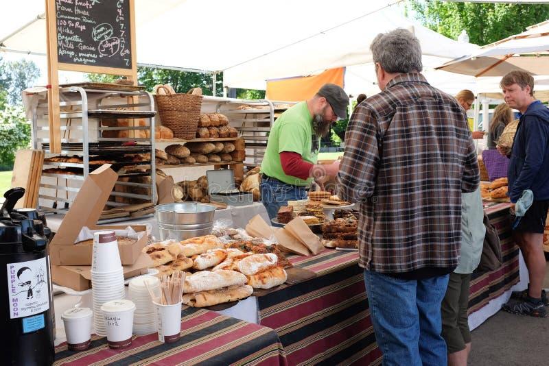 Kunder väntar på service på bageriställningen på den Oregon bondemarknaden arkivfoton