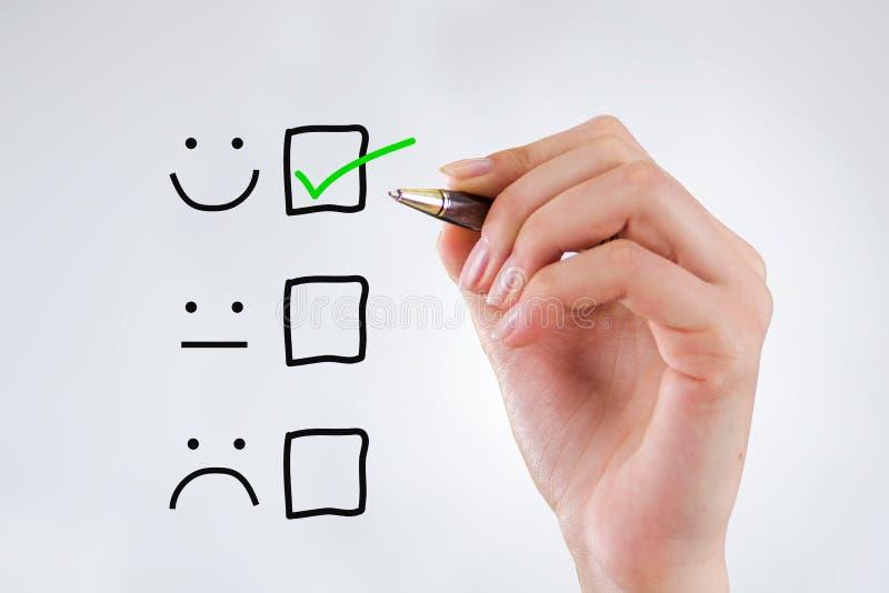 Kunderfarenhetsbegrepp, hand med en penna med en kontrollerad ask på utmärkta Smiley Face Rating för en tillfredsställelsegranskn arkivbild
