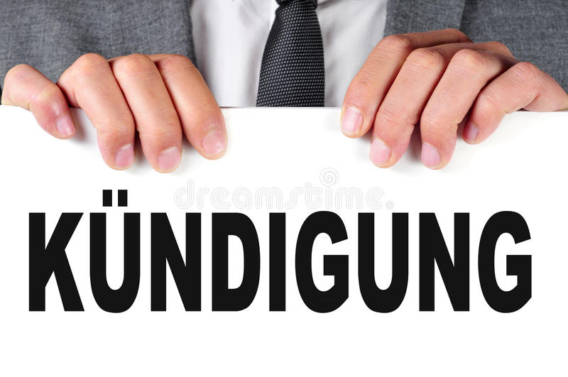 Kundigung, dismissal in german. A businessman showing a signboard with the word kundigung, dismissal in german, written in it royalty free stock image