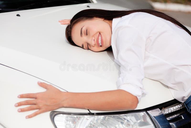 Kundin umarmt eine Haube ihres Neuwagens lizenzfreies stockbild
