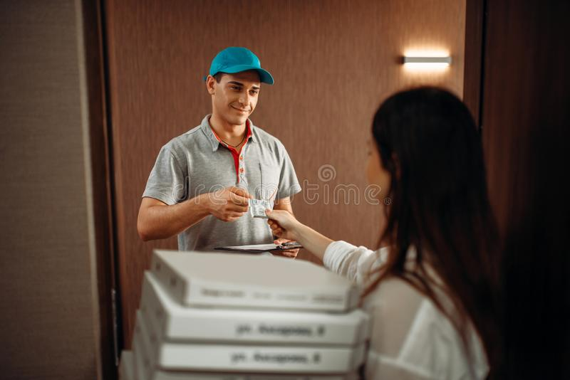 Kundspets till kuriren för snabb leverans av pizza royaltyfri foto