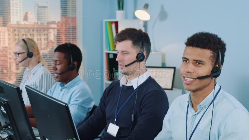 Kundsupportagent för blandad etnicitet som talar på telefon med headset arkivfoton