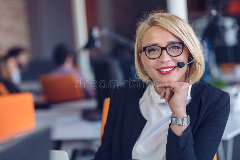 Kundtjänstrepresentant på arbete Härlig ung kvinna i hörlurar med mikrofon som arbetar på datoren royaltyfria foton