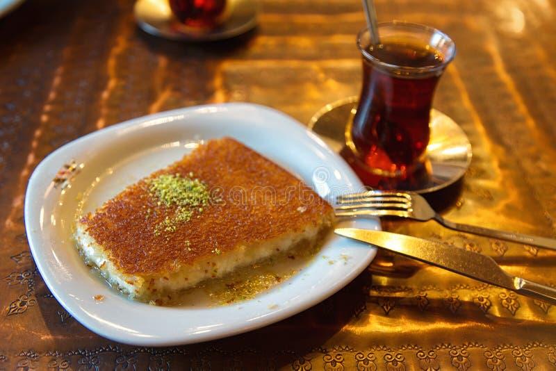Kunefe turc de dessert avec la poudre et le thé de pistache photographie stock libre de droits