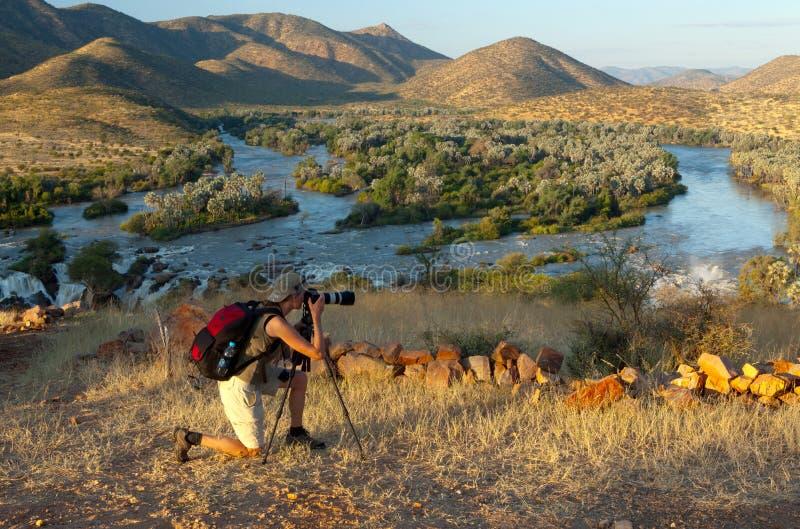 Kunene river, Namibia. Women taking picture with tripod. Epupa falls, Kunene river, Namibia, during the dusk stock photo