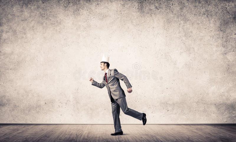 Kung affärsman i elegant kostym som springer i tomma rum med trägolv arkivfoto