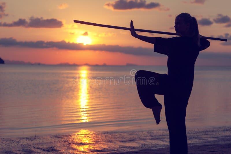 Kung-fu fazendo louro da mulher bonita nova da menina com a vara de bambu no litoral no por do sol, luta fotografia de stock royalty free