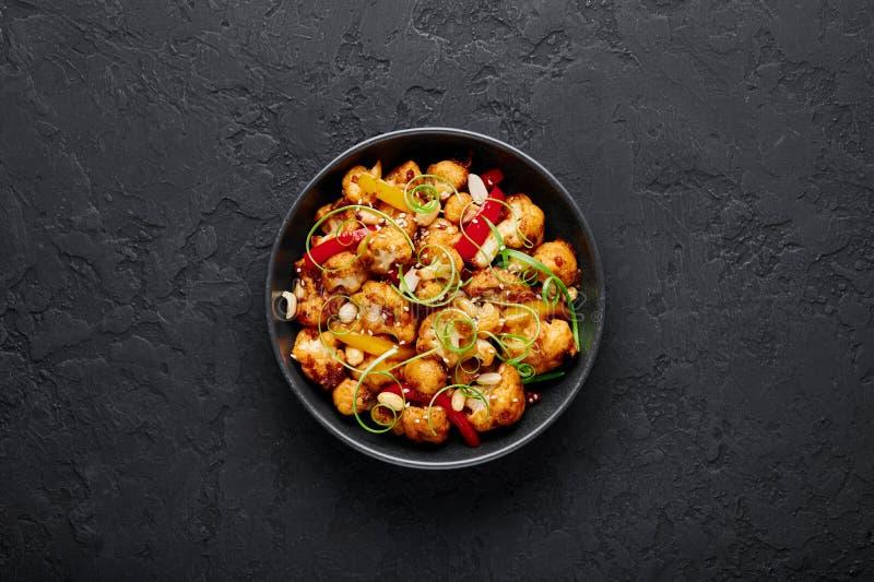 Kung Pao Cauliflower op donkere leisteenachtergrond Sichuan Kung Pao Cauliflower is een Chinees vegetarisch gerecht voor de keuke stock afbeelding