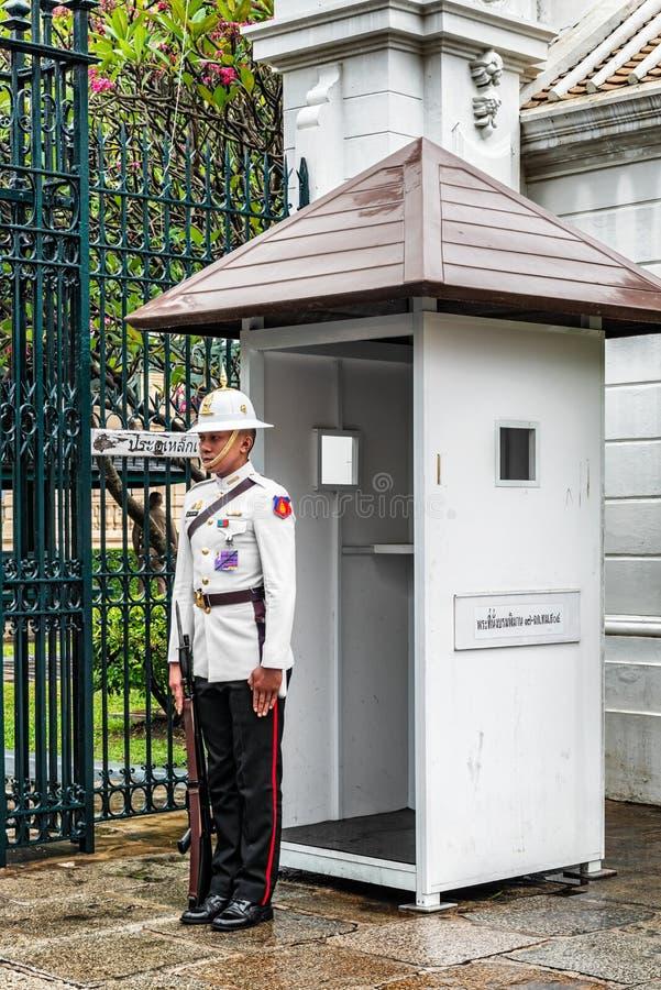 Kunglig vakt på porten till den storslagna slotten och Wat Pra Kaew, Bangk arkivbilder