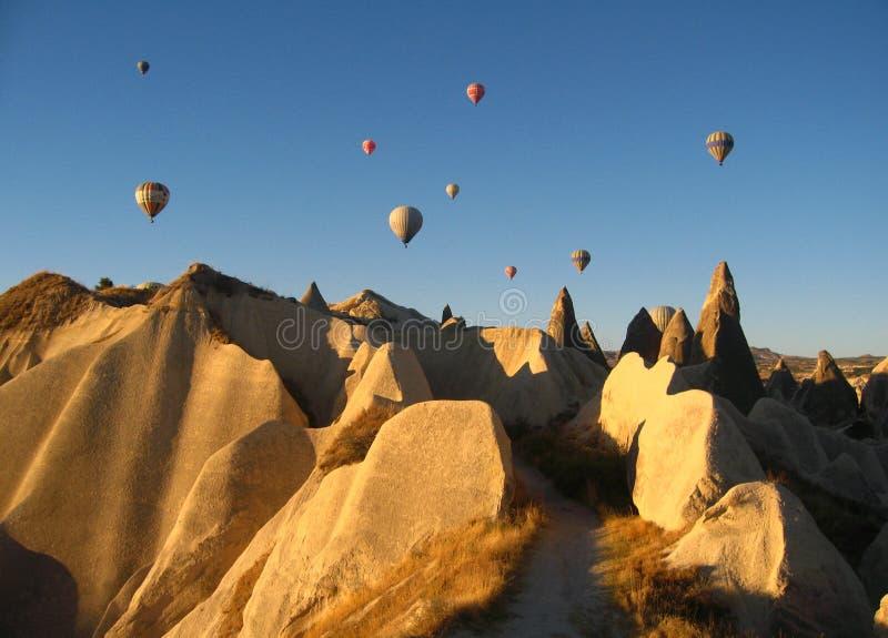 Kungliga ballons som flyger i soluppgången, tänder i Cappadocia, Turkiet ovanför den felika ChimneysÂenvaggar formationnärligg arkivbilder