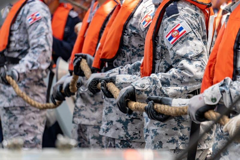 Kungliga thailändska marinsjömän i kamouflagemodelllikformig med flytvästen att dra det manila repet under påfyllning på havsövni arkivbilder