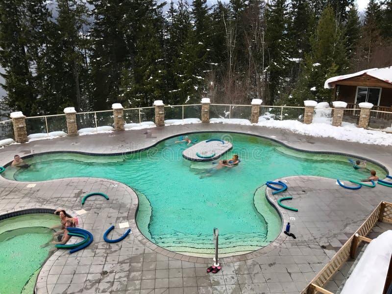 KUNGSFISKARE HOT SPRINGS, BRITTISKA COLUMBIA/KANADA - DECEMBER 26, 2016: Folk som kopplar av i 37 grader celsius mineralisk pöl royaltyfri fotografi