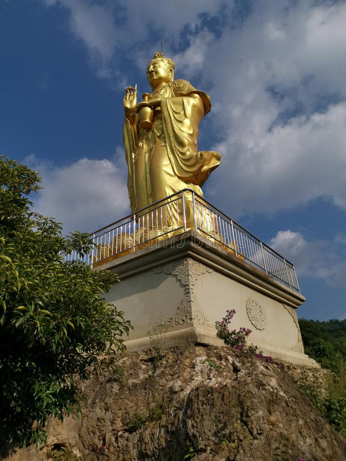 Mountain golden buddha shining in the sunlight against blue cloudy sky royalty free stock photo