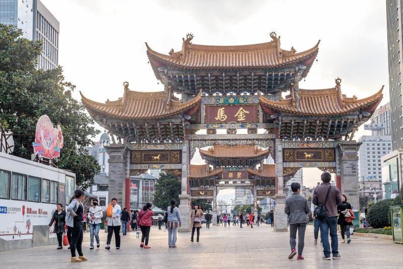 KUNMING 13 DE MARZO DE 2016 : La gente en los arcos conmemorativos de Jade Rooster y del caballo de oro, provincia de Kunming, Yu fotos de archivo