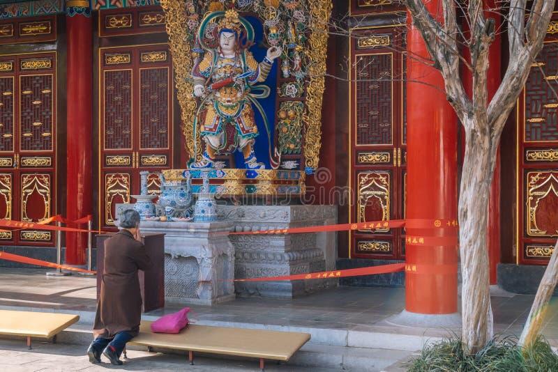 KUNMING 13 DE MARZO DE 2016 La mujer mayor está rogando en el templo budista de Yuantong, fotografía de archivo
